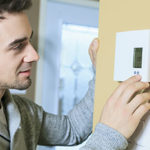 Man checking thermostat